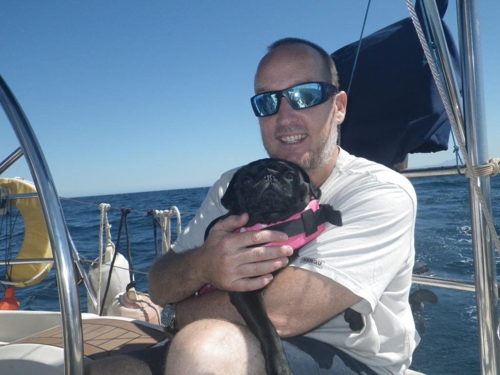 Man holding black dog in life vest on sailboat