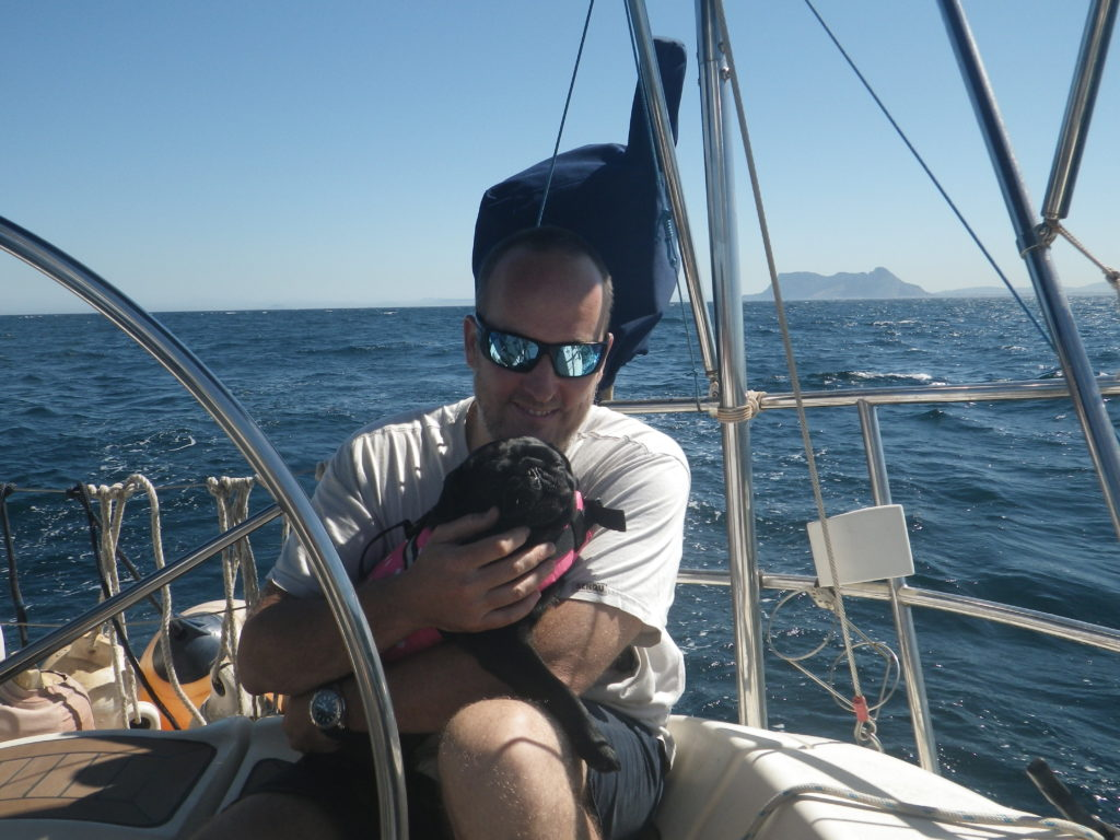 Dog on board a sailboat with the rock of Gibraltar in the background