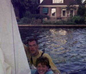 two people hoisting sail