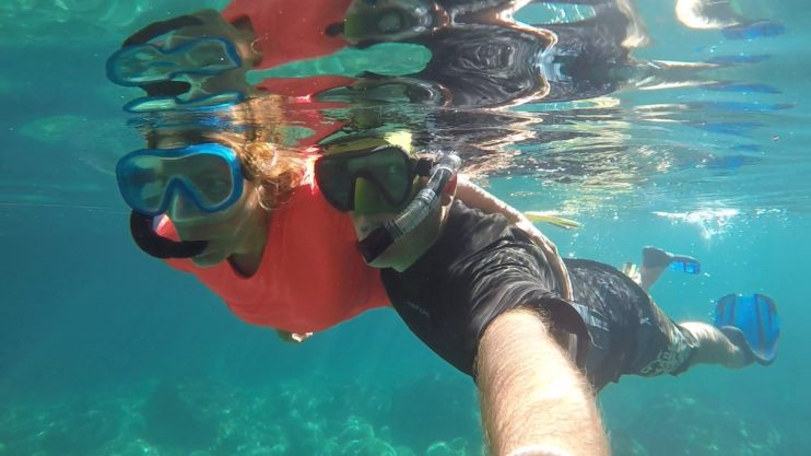 Two people snorkelling under water side by side